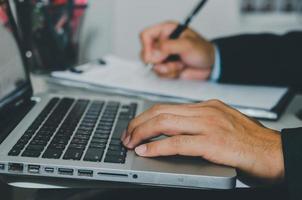 Cerrar la mano escribiendo en el teclado de la computadora portátil foto