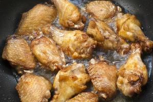 alitas de pollo friendo en la sartén foto