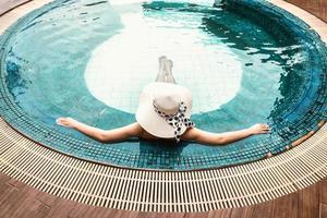 mujer en traje de baño se está relajando en la piscina foto