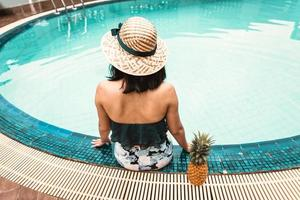 vista trasera, de, sexy, mujer, en, traje de baño, relajante, en, piscina foto