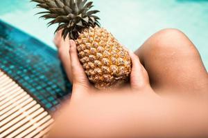 La mujer se está relajando en la piscina mientras sostiene la piña foto