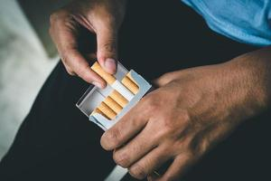 Close up man hand holding peel it off cigarette photo