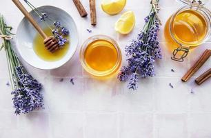 frascos y cuenco con miel y flores frescas de lavanda foto