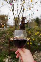Woman holding glass of red wine outside photo