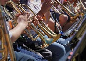 Gente tocando trompetas en la sección de latón. foto