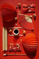 Flat lay of Japanese fans and decorative Chinese objects on red background photo