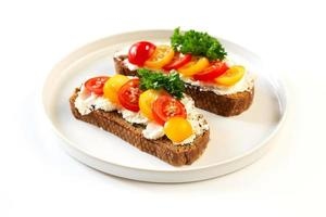 Two sandwiches with soft cheese and tomatoes photo