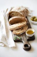Sliced loaf of bread on a cutting board. Olive oil, olives and basil photo