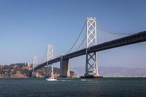 Landscape of San Francisco - Oakland bay bridge with running boat. photo