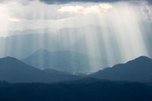 Dramatic sunlight from cloudy sky shining to dark blue mountain range. photo