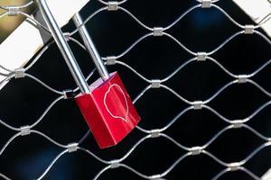 Cerradura roja con corazón de dibujo encerrado en jaula de red de acero. foto