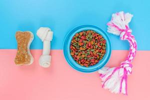 Pet food in blue bowl with accessories on color background photo