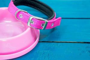 Pet collars and Bowls of pink on wooden background. photo