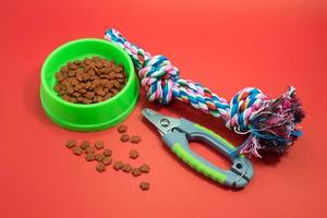 Bowls with food, Nail scissors and rope for bite on red background. photo