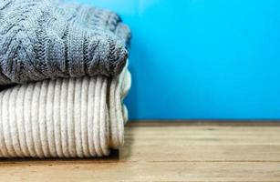 Stacked sweater with copy space on wooden table photo