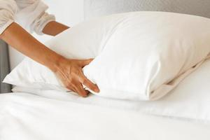 mano femenina configurar sábana blanca en el dormitorio foto