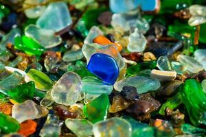 Natural background with sea glass close-up on sand. photo