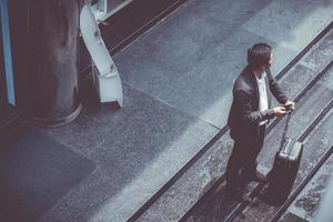Asian business man wear suit talking smart phone and holding suitcase. photo