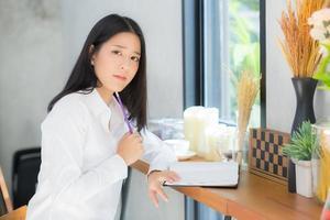 mujer joven que trabaja en línea con la computadora portátil y piensa en el proyecto. foto