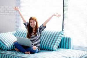 hermoso retrato de la felicidad de la mujer asiática joven que usa el trabajo portátil con éxito en el sofá en el hogar, la niña y el cuaderno de Internet en línea con el concepto de comunicación alegre. foto