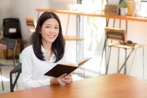 hermosa de retrato de negocios asiática joven leyendo en un cuaderno con éxito en la mesa, una chica mirando una nota emocionada en la cafetería, el concepto independiente y la educación. foto