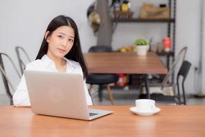 mujer asiática joven que trabaja en línea en la computadora portátil que se sienta en el café. foto