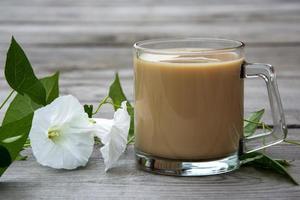 taza con cacao y loach con flores blancas sobre un fondo de madera. foto