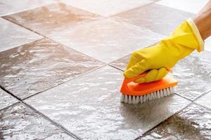 usando una fregadora de piso de plástico para fregar el piso de baldosas. foto