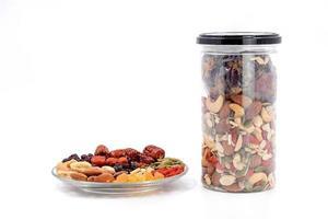 cereales integrales y frutos secos en un plato de vidrio y una botella de plástico. foto
