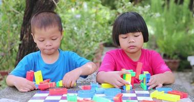 A girl and a brother are playing with plastic puzzles video