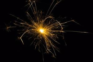Fireworks in flames on a black background. Christmas glitter. photo