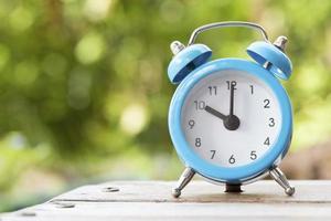 Despertador azul y blanco sobre la mesa de madera. foto