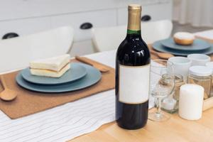 Drinking wine bottle on dining table. Beverage and food concept. photo
