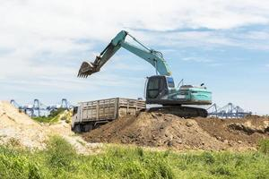 Digger car load and transfer soil to truck photo
