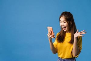 Señora asiática que usa la expresión positiva del teléfono móvil en fondo azul. foto