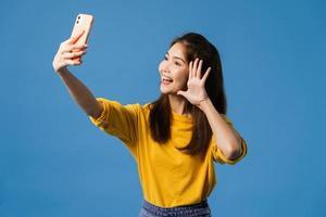 Asian female making selfie photo on smart phone on blue background.