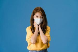 Joven asiática usa mascarilla, cansada del estrés sobre fondo azul. foto