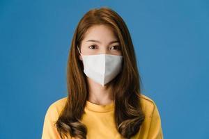 joven asiática con mascarilla médica sobre fondo azul. foto