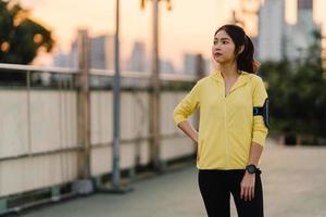 Asia atleta dama ejercicios haciendo ejercicios de estiramiento en urbano. foto