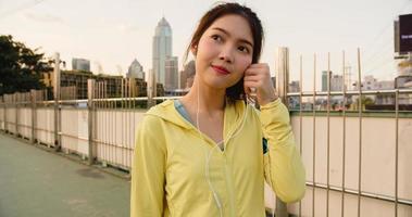 Asia atleta dama ejercicios con teléfono inteligente para escuchar música. foto