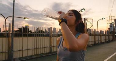 Asia athlete lady exercises drinking water after running. photo