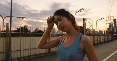 Asian athlete lady exercises because feel tired after running. photo