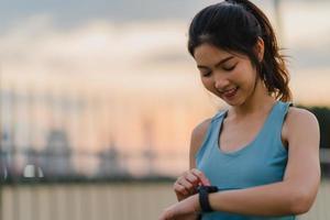Asia atleta dama ejercicios de comprobación del monitor de frecuencia cardíaca en el reloj inteligente. foto