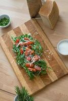 Arugula salad with cherry tomatoes and parmesan cheese photo