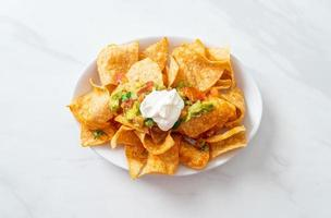 Nachos tortilla chips with jalapeno, guacamole, tomatoes salsa and dip photo