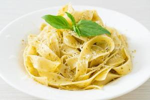 Pesto fettuccine pasta with parmesan cheese on top photo