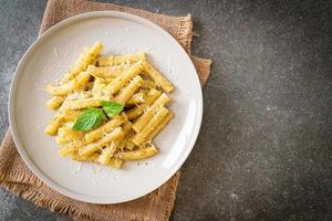 Pesto rigatoni pasta with parmesan cheese photo
