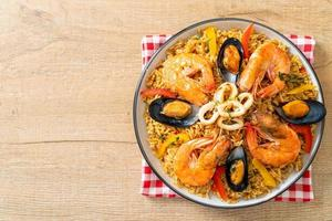 Seafood paella with prawns, clams, mussels on saffron rice photo