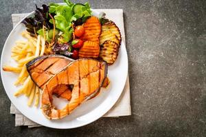 Grilled salmon steak fillet with vegetable and french fries photo