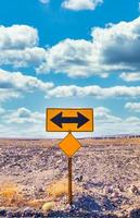 Directional sign in the desert with scenic blue sky photo
